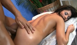 A black haired woman is getting a dick in her during a massage
