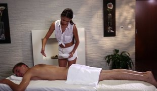 Masseuse gives him a handjob before riding his chunky strapon