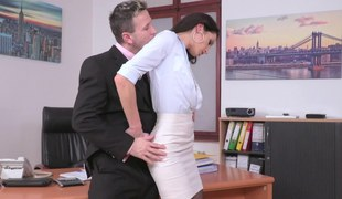 A babe is with her boss in the office and she's spreading her legs for him
